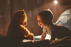 Happy baby laughing with teddy bear in bed. In the dark Stock Image