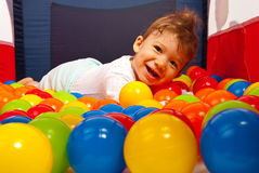 Happy baby laying on balls Royalty Free Stock Images