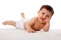 Happy baby laying with thumb in mouth Royalty Free Stock Images