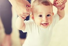 Happy baby learning to walk with mother help. Family, child, childhood and parenthood concept - close up of happy little baby learning to walk with mother help royalty free stock images