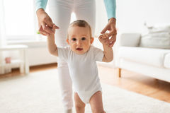 Happy baby learning to walk with mother help Royalty Free Stock Image