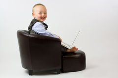 Happy baby in leather Chair with Laptop Stock Image