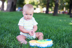 Happy baby with light and fluffy hair sitting on the grass and laughing. Royalty Free Stock Photography