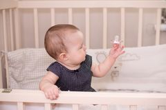 Happy baby little girl playing with a pacifier in her bed, at home royalty free stock image