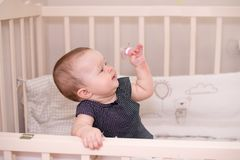 Happy baby little girl playing with a pacifier in her bed, at home. Copy space.  royalty free stock images