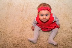 Happy baby look with curiousity sitting on floor. Happy baby girl in red dress look with curiousity sitting on the floor Royalty Free Stock Images