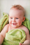 A happy baby lying on bed in green towel Royalty Free Stock Images