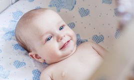 Happy baby lying in the cradle Stock Photography