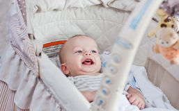 Happy baby lying in the cradle Royalty Free Stock Photo