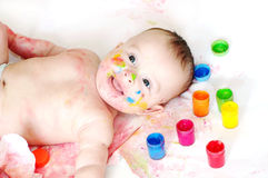 Happy baby lying among finger-type paints Royalty Free Stock Photo