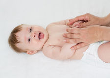 Happy baby lying getting massage Royalty Free Stock Photography