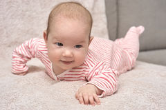 Happy baby lying on his stomach Stock Photo