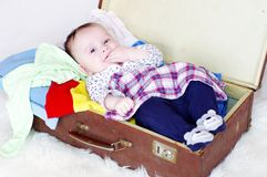 Happy baby lying in an old suitcase with clothes. The happy baby age of 5 months lying in an old suitcase with clothes royalty free stock photo