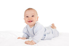 Happy baby lying on tummy. Happy and smiling baby lying on tummy on bed. Isolated on white Stock Photos