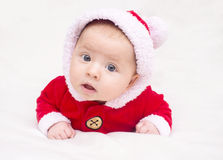 Happy baby lying on tummy wearing a red and white Christmas Santa suit Royalty Free Stock Photos