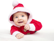 Happy baby lying on tummy wearing a red and white Christmas Santa suit Royalty Free Stock Images