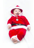 Happy baby lying on tummy wearing a red and white Christmas Santa suit Royalty Free Stock Image