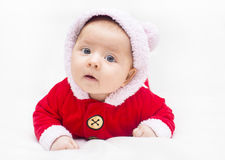 Happy baby lying on tummy wearing a red and white Christmas Santa suit Stock Images