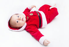 Happy baby lying on tummy wearing a red and white Christmas Santa suit Stock Photo