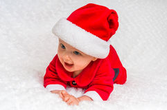Happy baby lying on white blanket with santa hat and suit Stock Photography