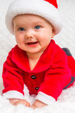 Happy baby lying on white blanket with santa hat and suit Stock Photos