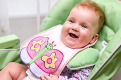 Happy baby before meal. Portrait of a happy baby girl with a feeder (bib)  smiling before meal Stock Photography
