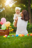 Happy baby and mom are playing in the green park Stock Image