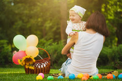 Happy baby and mom are playing in the green park Royalty Free Stock Photos