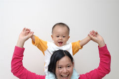 Happy baby on mother's shoulders. It is a cute chinese baby, he is on mother's shoulders, he is 10 months old Royalty Free Stock Image