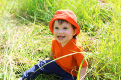 Happy baby in orange hat sitting on grass Stock Photo