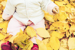 Happy baby outdoor at autumn park sitting on yellow leaves Stock Photo