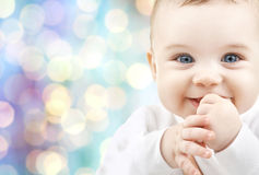 Happy baby over blue holidays lights background. Children, people, infancy and age concept - beautiful happy baby boy over blue holidays lights background stock image