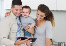 Happy baby with parents using digital tablet. Happy baby boy with parents using digital tablet in kitchen stock photography