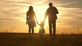 Happy baby and parents are walking at sunset. Silhouette of a family walking in the sun. Mom dad and kid. The concept of. A happy family. Family lifestyle stock video