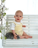 Happy Baby Petting Bunny. Baby boy with bunny sitting on swing looking at camera Royalty Free Stock Photography