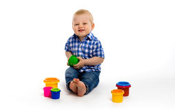 Happy baby in a plaid shirt with toys. studio Stock Images