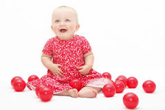 Happy baby playing. Happy baby girl playing with red balls stock images