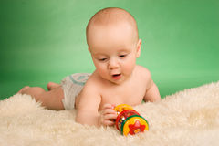 Happy baby playing. Happy baby lie on carpet and playing Royalty Free Stock Image