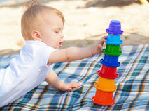 Happy baby playing on the beach. Stock Photos