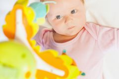 Happy baby playing with children's musical mobile toy Royalty Free Stock Photography