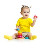 Happy baby playing with colorful wood pyramid or Royalty Free Stock Image