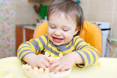 Happy baby playing with corn curls Royalty Free Stock Images