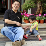 Happy baby is playing with his father. In a park Stock Images