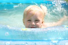 Happy Baby Playing in Swimming Pool. A happy baby boy is peeking over the edge of a swimming pool as he plays in the water on a summer day stock photos