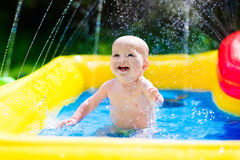 Happy baby playing in swimming pool Royalty Free Stock Images