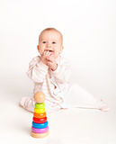 Happy baby playing with a toy pyramid  Stock Photos