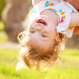 Happy baby playing upside down. Royalty Free Stock Photo
