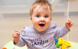 Happy baby in playpen. Portrait of a happy baby girl sitting in a playpen Royalty Free Stock Images