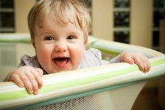 Happy baby in playpen. Portrait of happy baby girl looking over edge of playpen Stock Image