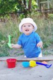 Happy baby plays with sand. Happy baby age of 10 months plays with sand Royalty Free Stock Photos